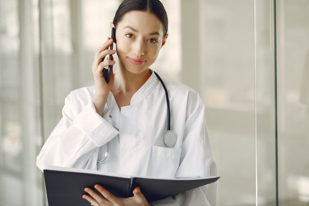 positive doctor in medical uniform talking on cellphone in 4173249
